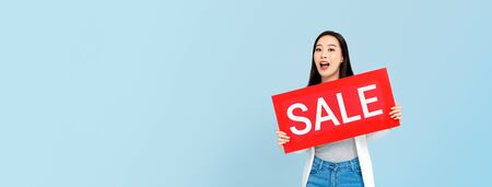Surprised Asian woman holding sale sign isolated on blue banner background with copy space