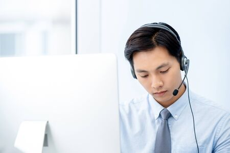 Handsome Asian telemarketing staff wearing headset concentrating on working in office