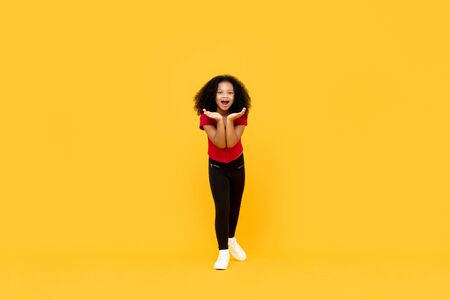Mixed race Afro girl in surprised excited gesture with hands open isolated on yellow background