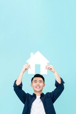 Happy young Asian man holding house sign with copy space  overhead isolated on light blue background for real estate concepts Stock fotó