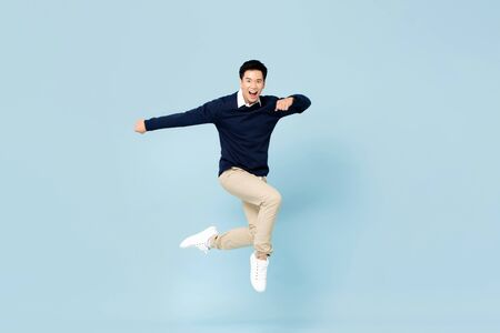 Young handsome Asian man smiling and jumping in mid-air on light blue studio background