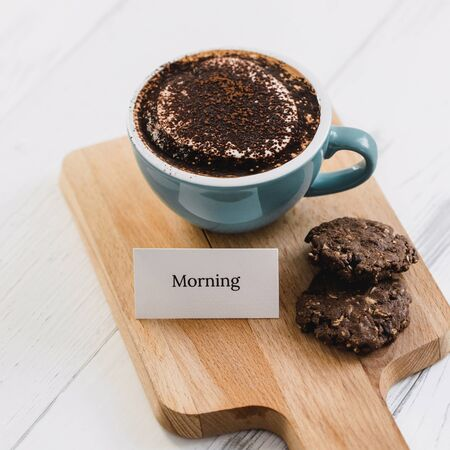 Cup of coffee with dark chocolate cookies and greeting message on wood platter in cafe Stock fotó