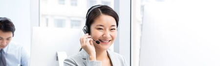 Banner of  smiling beautiful Asian woman working in call center office as a telemarketing operator