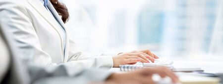 Hands of woman white collar workers typing on computer keyboards working in office, banner size