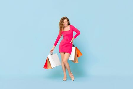 Smiling Caucasian woman with colorful shopping bags standing on light blue isolated background