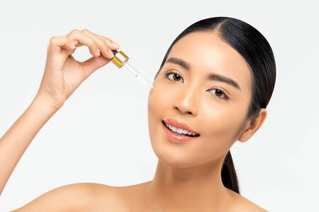 Beautiful Asian woman applying anti aging moisturizing serum on her face for beauty and skin care concepts Stock fotó