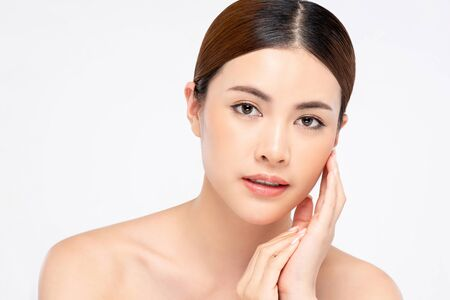 Close up of youthful radiant pretty Asian woman with hand touching face on white background for beauty and skin care concepts