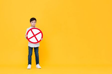 Full length portrait of Asian boy holding red stop or no sign in blank yellow isolated studio background Stock fotó