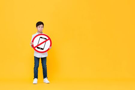 Portrait of standing young Asian boy holding banned cellphone usage sign in yellow isolated background with copy space Stock fotó
