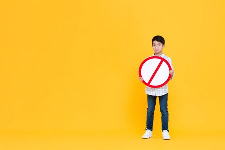 Portait of standing pouting young Asian boy holding red ban signage in yellow isolated studio background with copy space Stock fotó