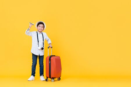 Young smiling Asian boy going on vacation holding toy airplane and luggage in yellow isolated studio background with copy space