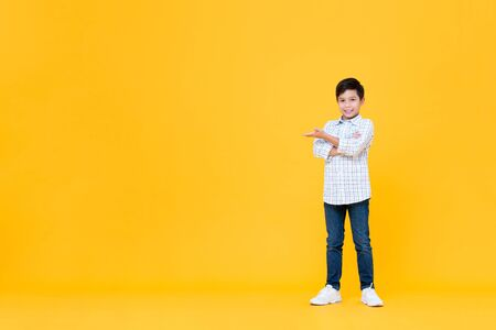 Full length portrait of smiling young Asian boy doing arms crossed gesture with open palm in yellow isolated background with copy space