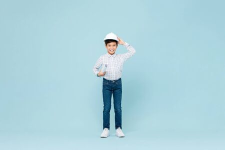 Full length portrait of smiling young asian boy aspiring to be future engineer wearing white hardhat holding blueprint in blue isolated studio background