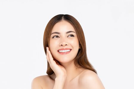 Cheerful beautiful smiling Asian woman with clear fair skin doing hand touching face pose while looking up in white isolated background