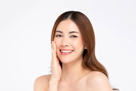 Beauty shot of smiling Asian woman model with clear fair skin doing hand touching face pose in white isolated background for skincare concept Stock fotó