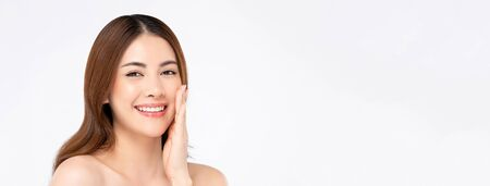 Happy confident beautiful smiling Asian woman model with clear fair skin doing hand touching face pose in white isolated banner  background with copy space Stock fotó
