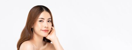Beauty shot of Asian woman model with clear fair skin doing hand touching face pose in white isolated banner background for skincare concept