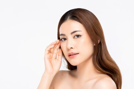 Beauty shot of Asian woman model with clear fair skin doing hand touching face pose in white isolated background for skincare concept