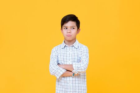 Sulky bored boy pouting mouth and thinking with arm crossed gesture isolated yellow background