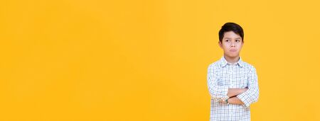 Sulky bored boy pouting mouth and thinking with arm crossed gesture isolated yellow banner background