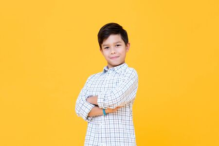 Happy smiling boy with arm crossed gesture isolated on yellow background