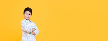 Happy smiling boy with arm crossed gesture isolated on yellow banner background with copy space