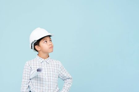 Doubt engineer boy with white helmet looking upward isolated on light blue background Stock fotó