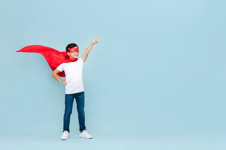 Smiling superhero boy in red mask and cape pointing hand aside isolated light blue background
