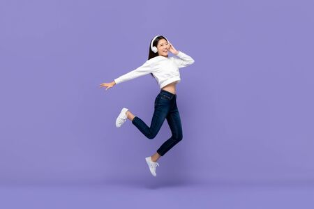 Happy young Asian woman jumping and listening to music on headphones isolated on purple background