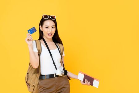 Beautiful Asian tourist woman in yellow background holding passport and boarding pass ready to travel with credit card Stock fotó - 145324447
