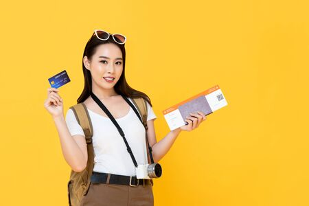 Beautiful Asian tourist woman in yellow background holding passport and boarding pass ready to travel with credit card