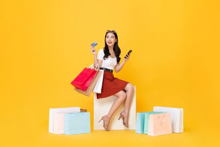 Beautiful Asian woman sitting and carrying shopping bags with credit card and mobile phone in hands on yellow background Foto de archivo