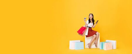 Beautiful Asian woman sitting and carrying shopping bags with credit card and mobile phone in hands on yellow banner background