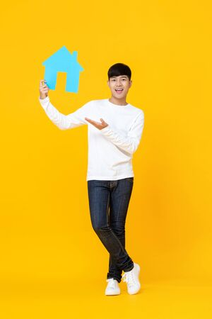 Smiling handsome Asian man holding house sign with hand presenting gesture isolated on yellow background Stock fotó - 145324420