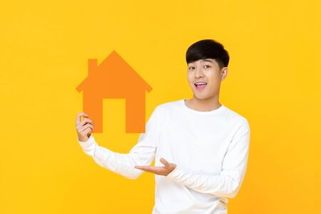 Smiling handsome Asian man holding house sign with hand presenting gesture isolated on yellow background
