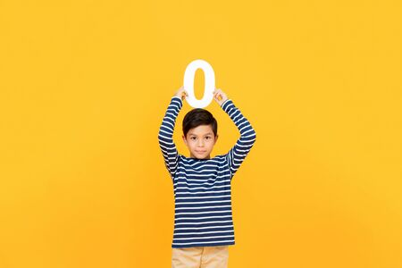 10 year-old cute little boy holding number zero overhead on yellow background Stock fotó - 145324424