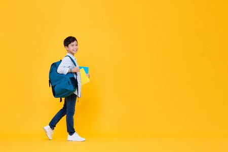 Smiling handsome 10 year-old schoolboy holding books and backpack walking in yellow studio background for education concept 版權商用圖片 - 145324426