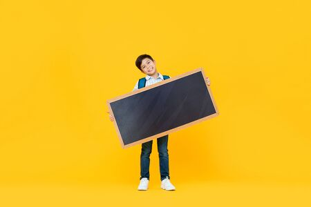 Smiling handsome 10 year-old mixed race boy holding empty blackboard isolated on yellow studio background for education concept 版權商用圖片 - 145324427