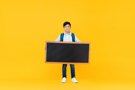 Smiling handsome 10 year-old mixed race boy holding empty blackboard isolated on yellow studio background for education concept 版權商用圖片 - 145324428