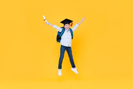 Handsome schoolboy with graduate cap smiling and jumping on yellow background for educatin concept 版權商用圖片