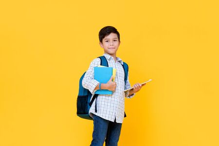 Handsome 10 year-old boy with backpack holding books and tablet computer in yellow background for education concept Stock fotó - 145324431