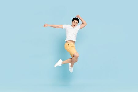 Happy handsome Asian young man in casual clothes smiling and jumping in light blue pastel background 版權商用圖片 - 145324438