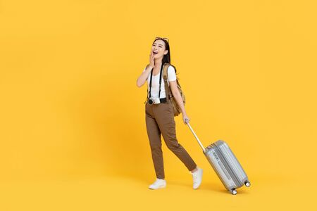 Happy young Asian tourist woman with baggage going to travel on holidays isolated on yellow background