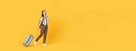 Happy young Asian tourist woman with baggage going to travel on holidays isolated on yellow banner background with copy space Stock fotó