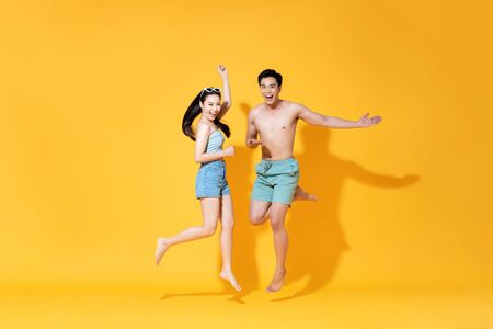 Energetic happy Asian couple in summer beach casual clothes jumping on yellow background studio shot Stock fotó - 145323748