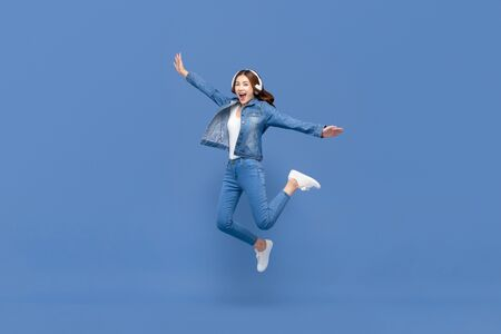 Happy young Asian woman jumping while listening to music on headphones isolated on blue studio background