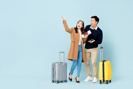 Lovely Asian couple tourists with baggage passports and boarding passes about to go for honeymoon travel 版權商用圖片