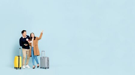Lovely Asian couple tourists with baggage  about to go for winter honeymoon travel isolated on light blue background with copy space
