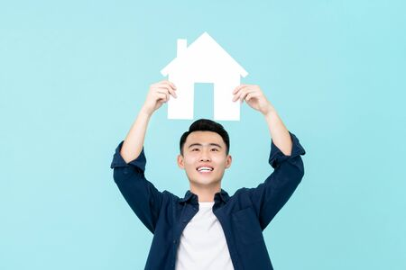 Happy young Asian man holding house sign overhead isolated on light blue background for real estate concepts