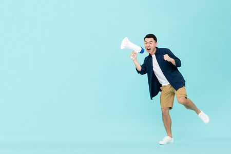 Excited young Asian man holding megaphone and shouting isolated on light blue background with copy space 版權商用圖片 - 145323758